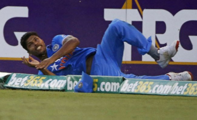 India\'s Umesh Yadav crashes on the boundary as he attempts to prevent four runs by England\'s...