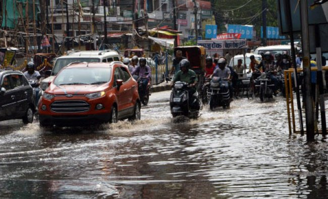 People move through a waterlogged road after heavy rains and storm in Patna on Monday. PTI Photo