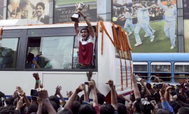 A Mohun Bagan player showing trophy to the football fans who gathered to welcome the team ...