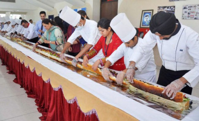 Hotel Management students making a giant 30 feet-long sandwich in Jalandhar on Monday. PTI Photo