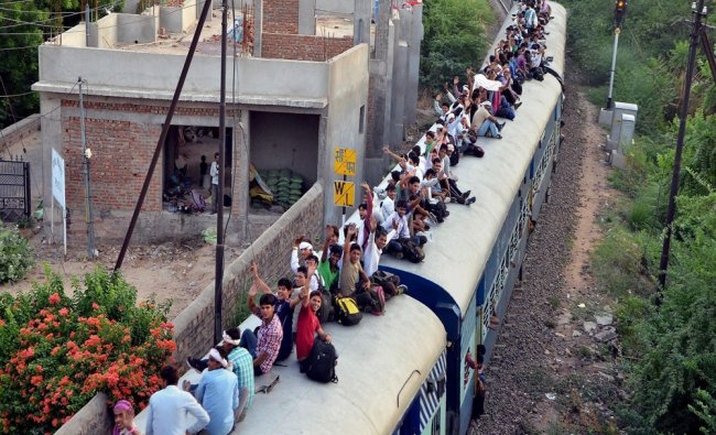 Army aspirants travel on the roof of a train in Jodhpur after participating recruitment rally...
