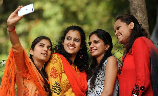 A girl takes selfie with her friends on the occasion of \'Friendship day\' near UB City in Bengaluru..