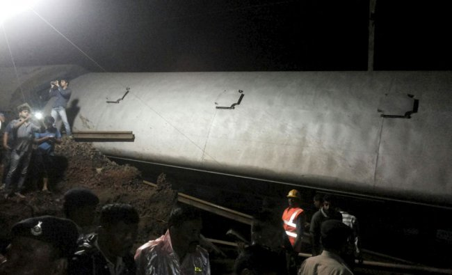 Police and members of the rescue operation stand at the site of a train derailment near Harda...