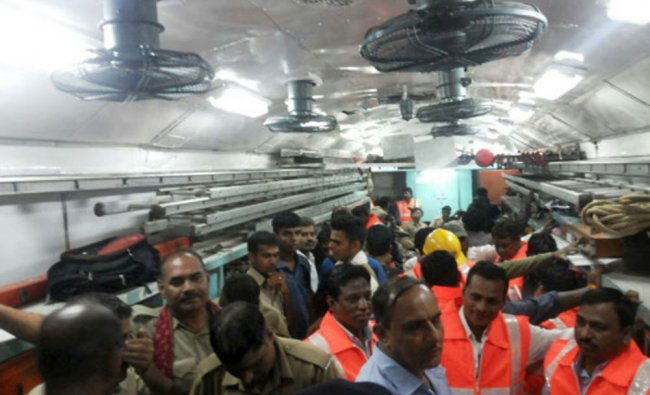 Officials and members of the rescue operation stand in a carriage of a derailed train near Harda...