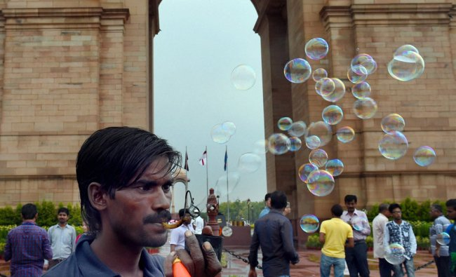 A vendor blows soap bubbles as he waits for customers during rains at India Gate...