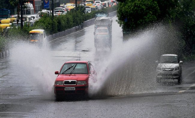 Vehicles move on a waterlogged road during downpour in New Delhi on Sunday...