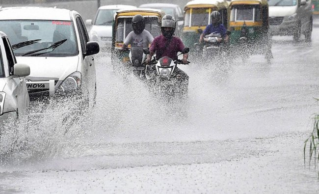 Vehicles move through a waterlogged road during the downpour in New Delhi on Sunday...