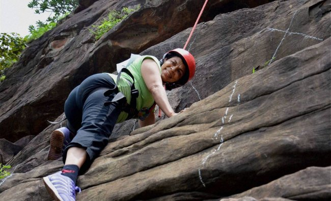 A woman rock climber takes part in an adventure sports camp...