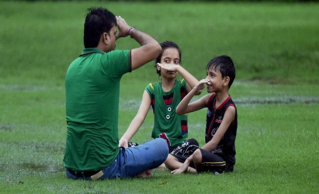A family doing yoga during drizzle at the India Gate lawn in New Delhi...