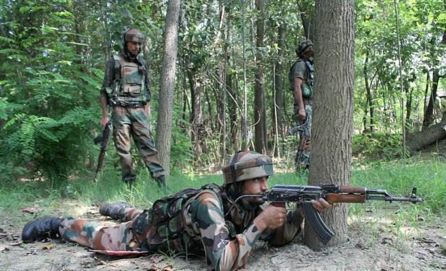Army jawans take positions during an encounter between security forces...