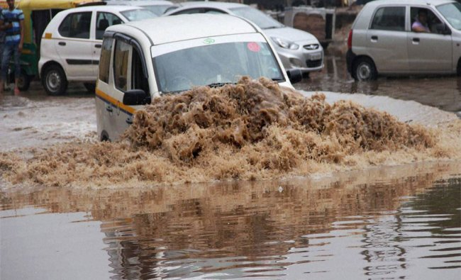 Vehicles wade through a water logged road after heavy rains in Gurgaon on Tuesday...