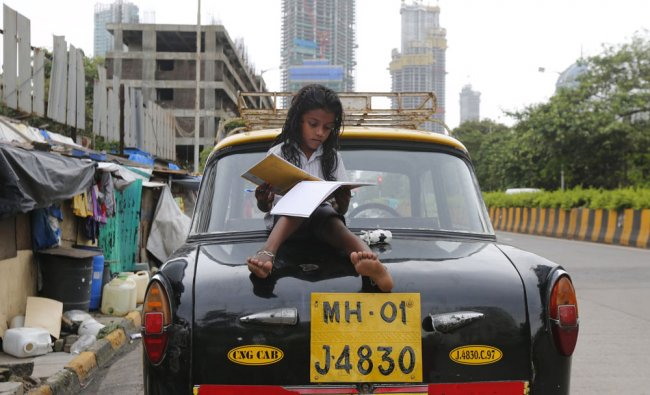 A girl studies while sitting on top of a taxi outside her shanty home at a roadside in Mumbai...
