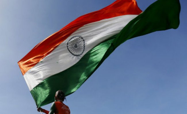 A supporter of the Indian cricket team waves the Indian national flag during the second day of...