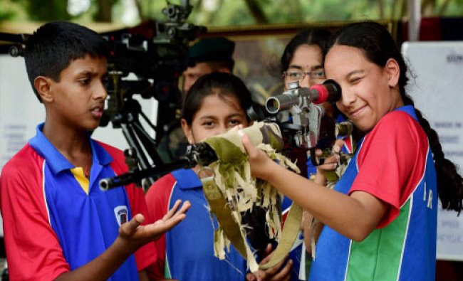 Students check a sniper rifle during a \'Know Your Army Mela\' in Bengaluru...