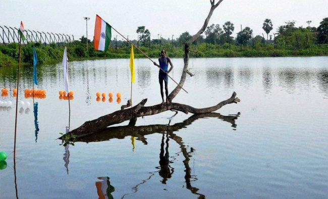 A man waves a Tricolour flag at a a tree in a lake near Indo Bangladesh border...