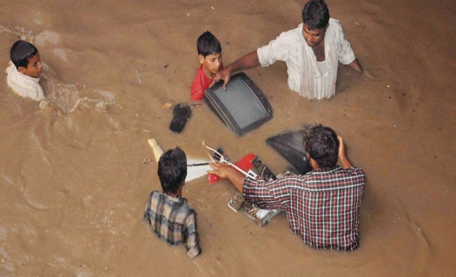 Peoples collecting articles flowing in flood after heavy rains in Faridabad on Sunday...