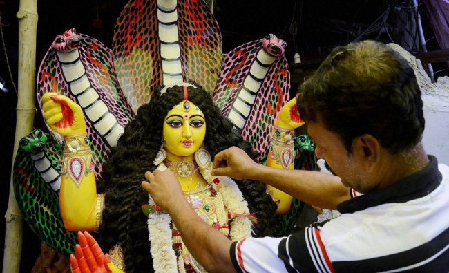 An artist giving finshing touch to idol of Goddess Manasha...