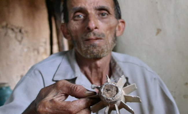 A man showing remains of a mortar shell fired by Pakistani rangers at Rajdhani sector...