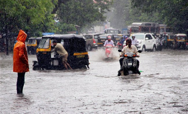 Vehicles move through a water-logged road during heavy rains in Thane...