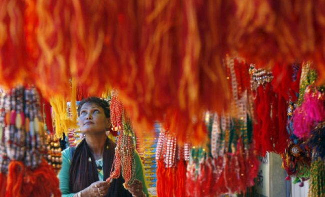 A woman buys \'rakhi\' or traditional Indian sacred thread, at a stall in a marketplace in Kolkata...