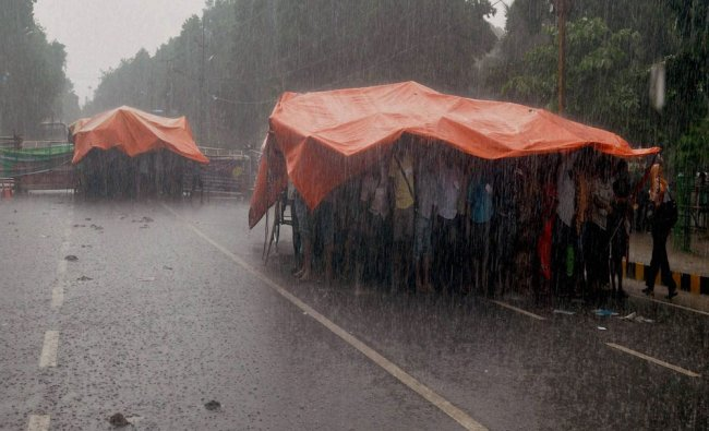 Protesters using polythene sheets to protect themselves from rains in Bhubaneswar...
