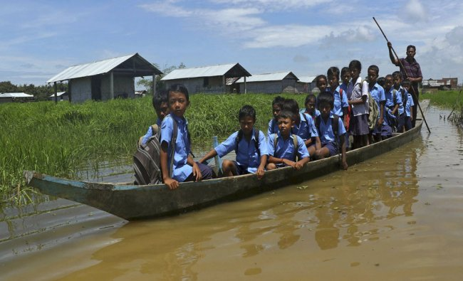 Flood-affected children use a boat to reach their school after incessant rains...