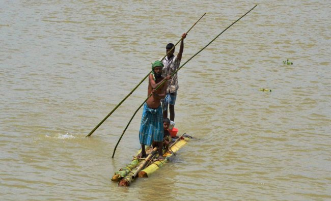 Villagers commute on a banana-raft in a flooded village in Morigaon district of Assam...