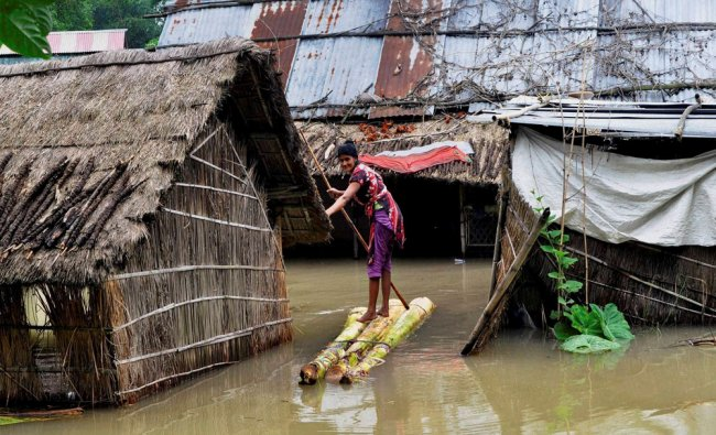 A woman crosses a flooded area over a raft made of banana tree trunks at Bura Bure...