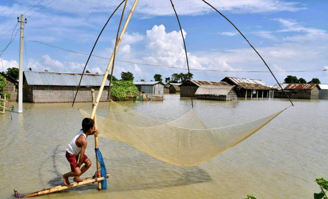 A boy prepares to cast fishing net in the flood waters next to submerged houses...