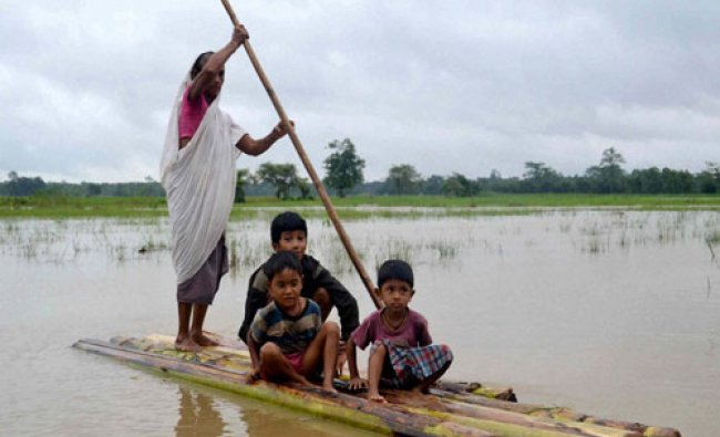 A woman crosses a flooded area over a raft made of banana tree trunks at Dhakuakhana in...