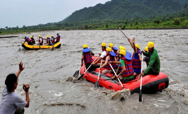 People take part in rafting at Bogamati, a picnic spot, in Baska district of Assam...