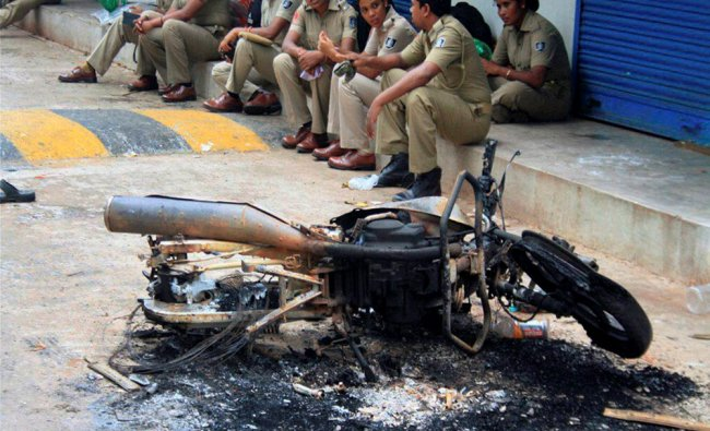 Police personnel sitting near the charred remains of a motorcyle near the violence-hit Trahi ...