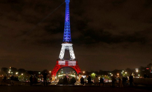 People look at the Eiffel Tower illuminated in the French colors in honor of the victims ...