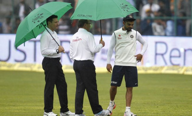 Kohli chats with umpires Kettleborough and Gould as they inspect the field...