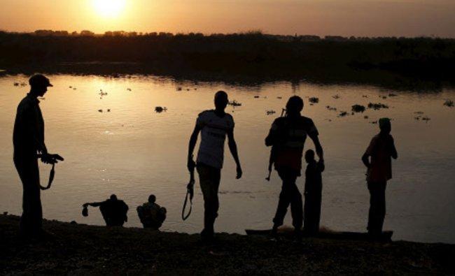 Rebel fighters walk after having morning wash in Sobat river...