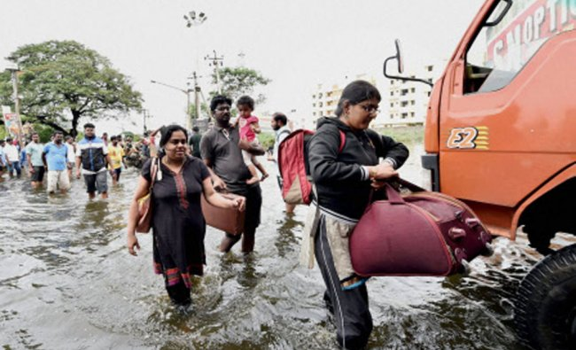 Flood affected people shift from an inundated locality following rains in Chennai ...