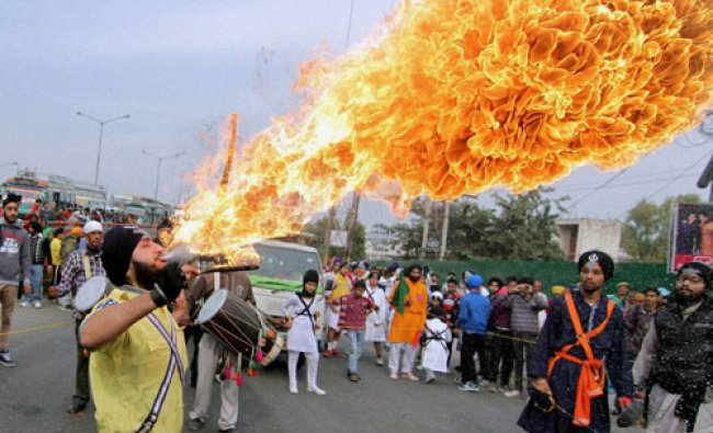A Sikh devotee performs with fire during a religious procession ahead of the birth anniversary...