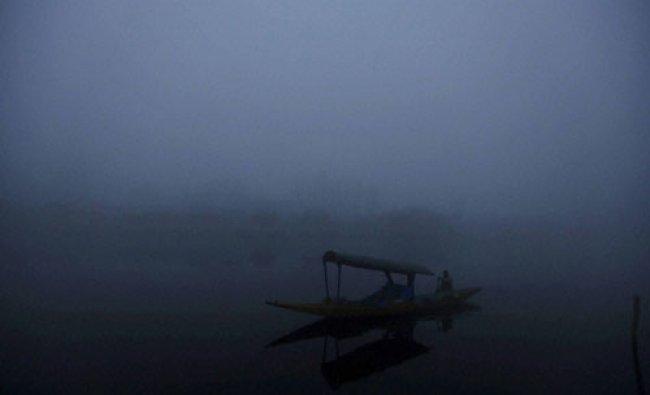 A man rows his shikara (boat) during a foggy morning at Dal Lake in Srinagar...