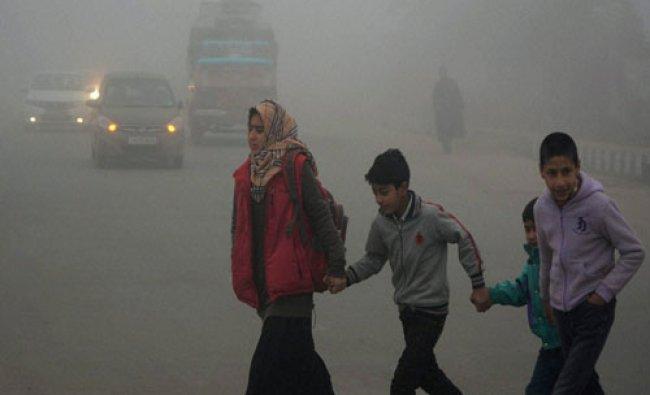 Children crossing a road during a foggy morning in Srinagar on...