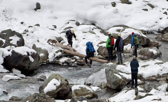Ice climbers crossing a stream with the help of a log at Chandanwari at tourist resort of...