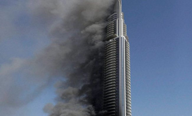 A fire burns on the Address Downtown skyscraper in Dubai, United Arab Emirates...