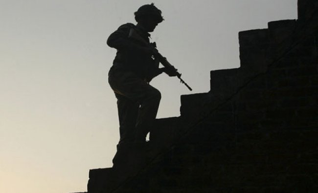 An Indian army soldier climbs up stairs to take his position on the rooftop of a residential...