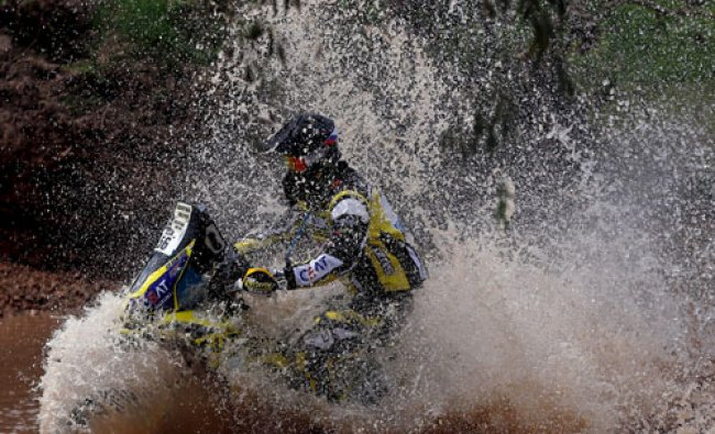 Shivashankar Chunchunguppe of India rides his Suzuki through the water during the...