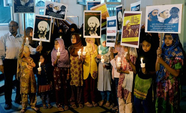 Shia Muslims hold candles and poster of...