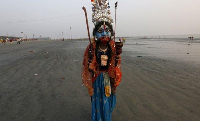 A man dressed as Hindu goddess Kali walks for alms from Hindu pilgrims ahead of the...