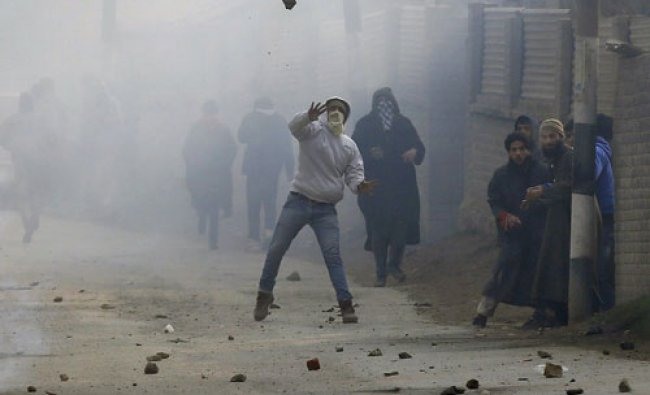 A protester throws a stone towards Indian police during a clash after the funeral of Bhat...