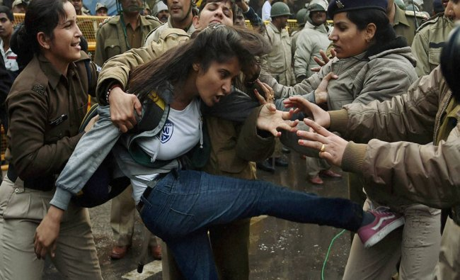 Police detain a girl student during a protest against HRD minister in New Delhi...