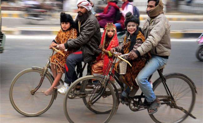 People ride their cycles with their children dressed as Hindu Gods in Allahabad...