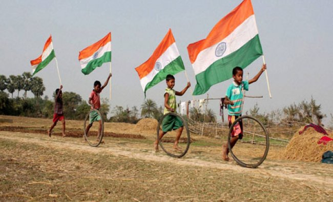 Village boys run with National flags ahead of Republic day celebrations at Balurghat in South ...