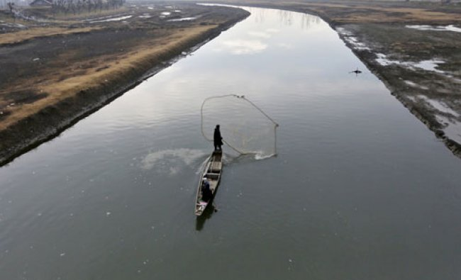 A fisherman casts his net in the waters of a flood channel on the outskirts of Srinagar...